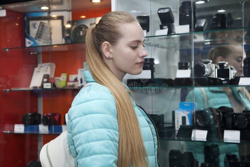 Nastoletnia dziewczyna stoi blisko gabloty wystawowej z fotografii kamerami fotografia royalty free