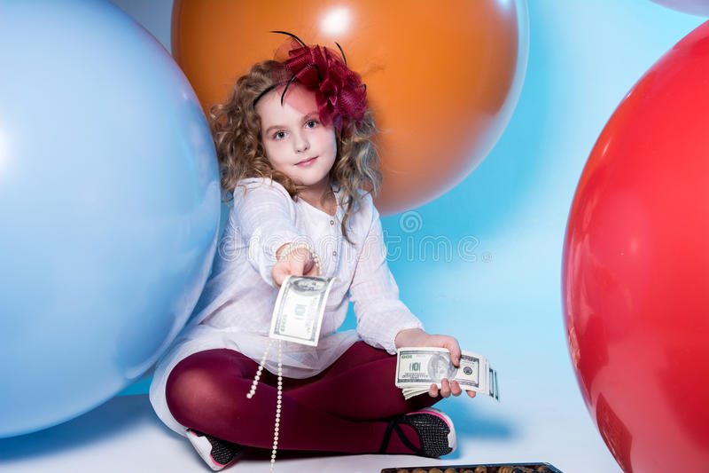 Nastoletnia dziewczyna trzyma zwitek 100 dolarowych rachunków w białej sukni zdjęcia royalty free