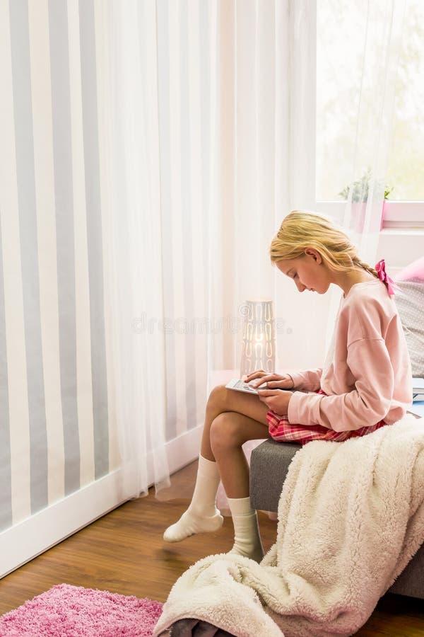 Nastoletnia dziewczyna używa pastylkę zdjęcie royalty free