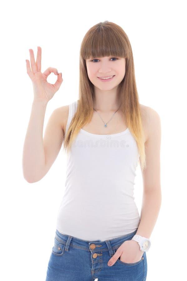 Nastoletnia dziewczyna w białej koszulce pokazuje ok znaka odizolowywającego na bielu zdjęcia royalty free