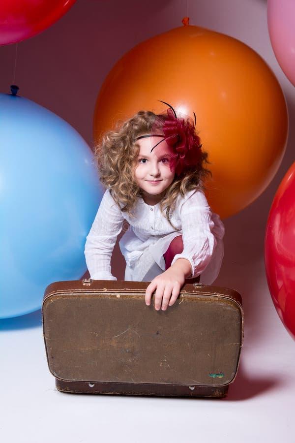 Nastoletnia dziewczyna w białej sukni z otwartą walizką zdjęcia stock