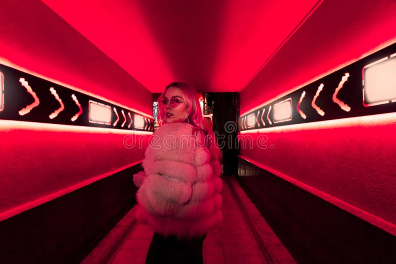 Nastoletnia dziewczyna w eleganckich szkłach i futerko w różowych neonowych światłach podpisujemy na ulicy ścianie obraz stock
