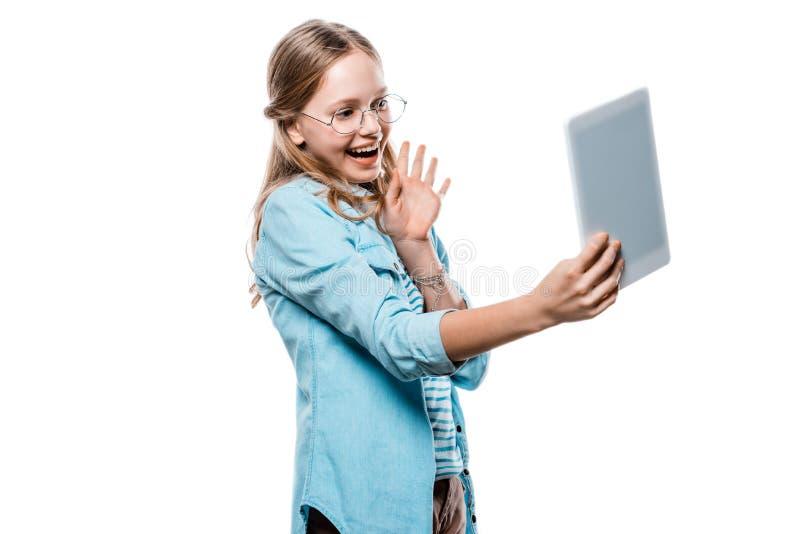 Nastoletnia dziewczyna w eyeglasses używać cyfrową pastylkę odizolowywającą na bielu obraz royalty free