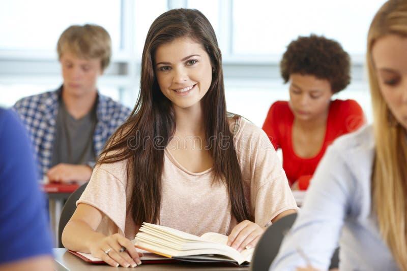 Nastoletnia dziewczyna w klasowy ono uśmiecha się kamera zdjęcie royalty free