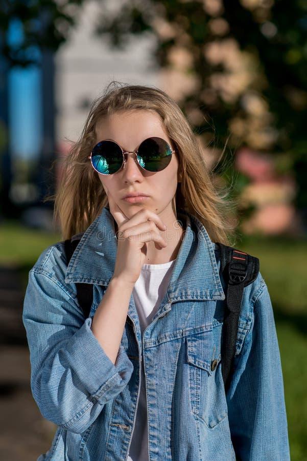 Nastoletnia dziewczyna w okularach przeciwsłonecznych pozuje przy kamerą Ubierał każdy dzień odziewa Blondynki lato w świeżym pow fotografia royalty free