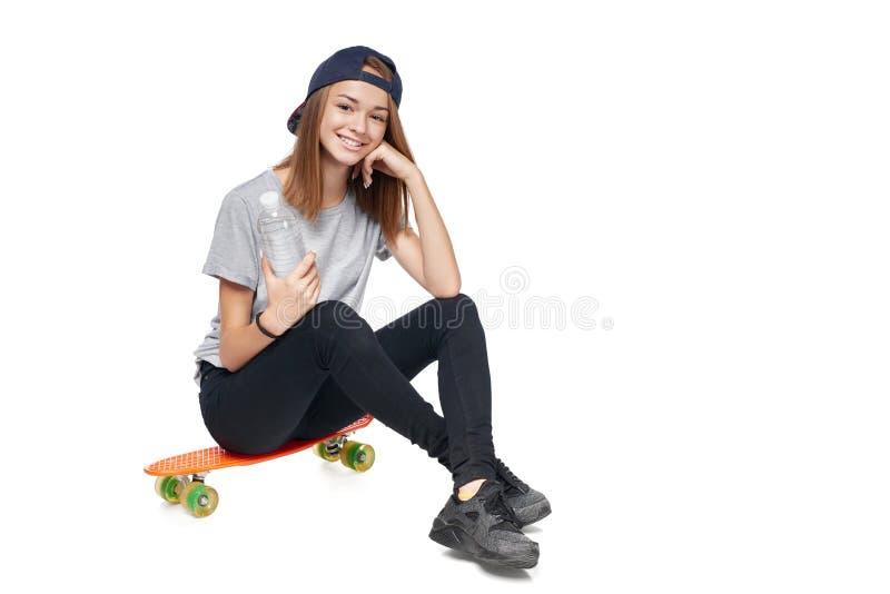 Nastoletnia dziewczyna w pełnym długości obsiadaniu na łyżwy desce obraz royalty free