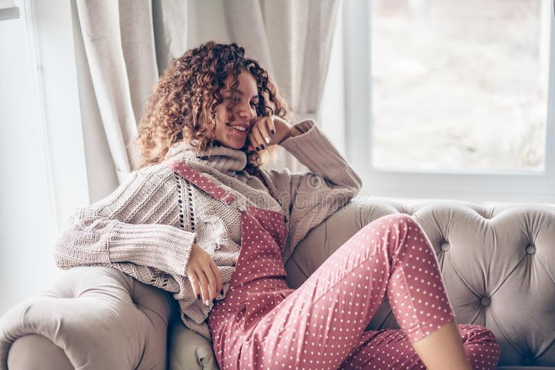 Nastoletnia dziewczyna w pulowerze i kombinezonie na leżance fotografia stock