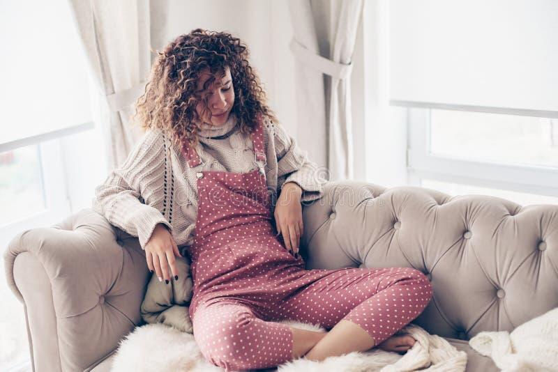 Nastoletnia dziewczyna w pulowerze i kombinezonie na leżance obraz royalty free