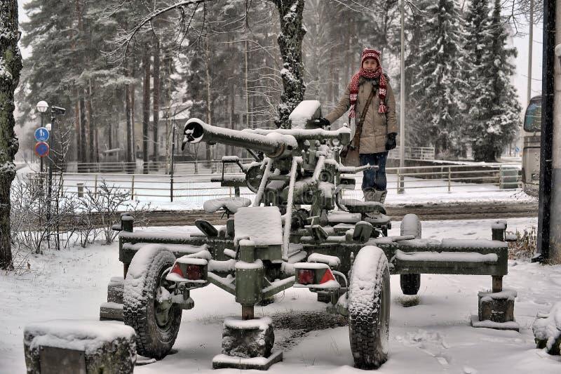 Nastoletnia dziewczyna w zimie blisko starego działa od drugiej wojny światowa fotografia stock