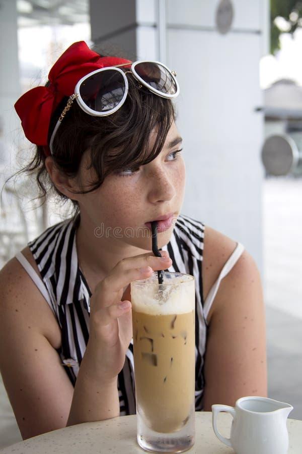 Nastoletnia dziewczyna z ładnymi piegami na ona twarz, napój lodowa kawa przez słomy w kawiarni blisko okno zdjęcia stock