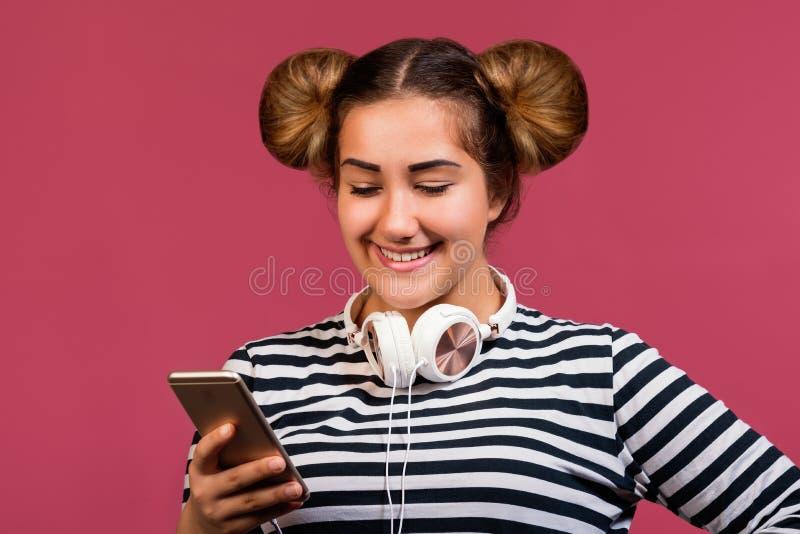 Nastoletnia dziewczyna z śmieszną fryzurą używa telefon słuchać muzykę na różowym tle zdjęcie stock