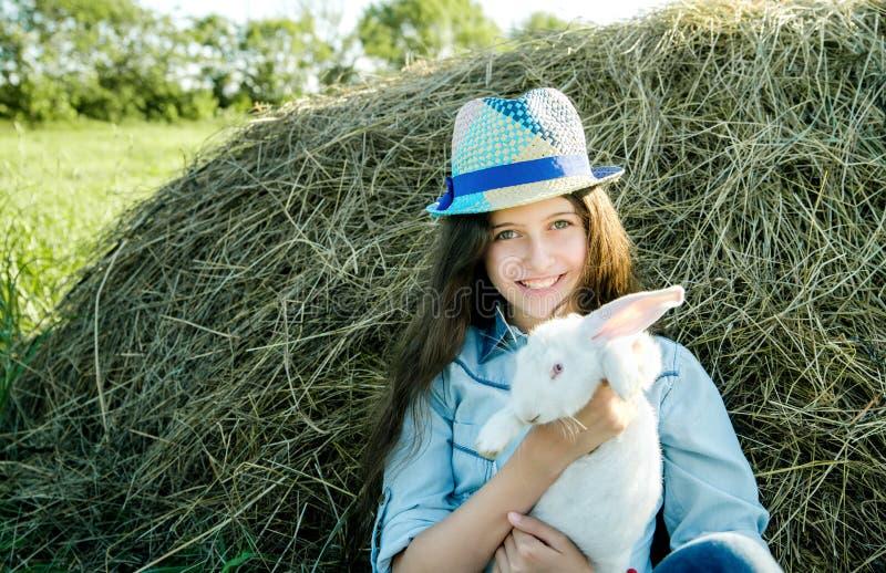 Nastoletnia dziewczyna z białym królika obsiadaniem przed haystack zdjęcie stock