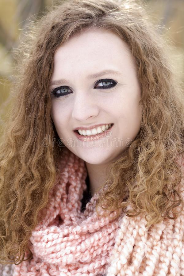 Nastoletnia dziewczyna z kędzierzawą brown włosianą jest ubranym brzoskwinią barwił cowl obraz stock