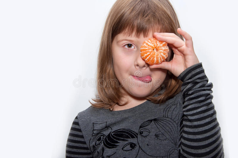 Nastoletnia dziewczyna z mandarynką pokazuje tonque fotografia stock