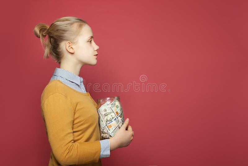 Nastoletnia dziewczyna z słojem pełno pieniądze gotówka Uczeń opłaty, odpowiedzialność i oszczędzanie pieniądze pojęcie, zdjęcia royalty free