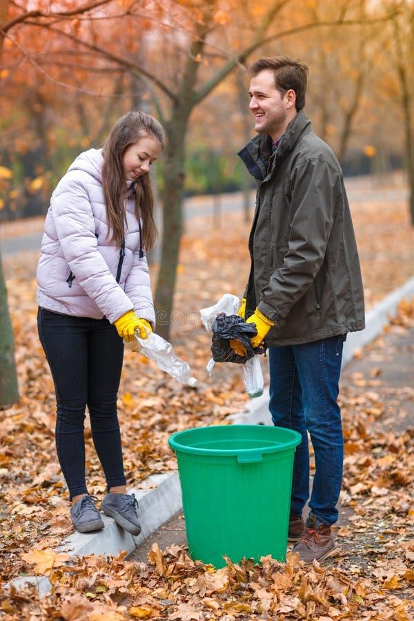 Nastoletnia dziewczyna z tata czystym w parku, rzucający out różnorodne torby i klingeryt butelki w łzawicy _ zdjęcia stock