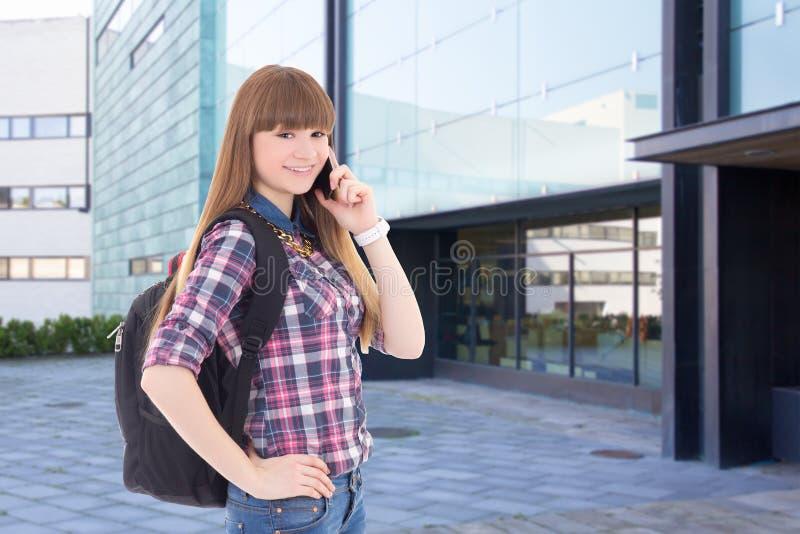 Nastoletnia dziewczyna z telefon komórkowy pozycją na ulicie przeciw szkolnemu b zdjęcia stock