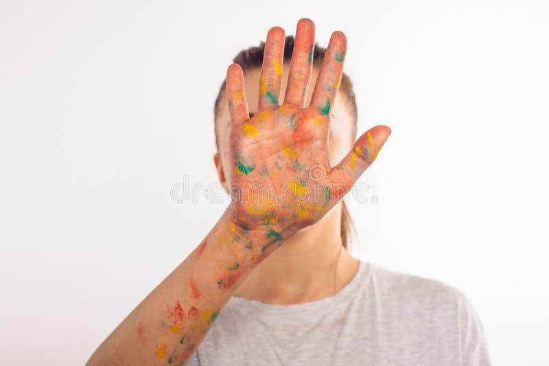 Nastoletnia dziewczyna zakrywa jej twarz z jej palmą w farbie zdjęcia royalty free