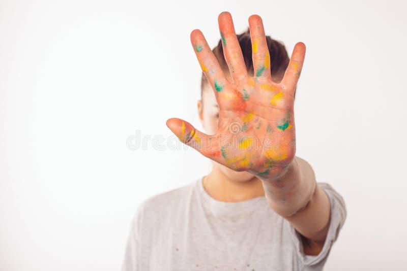 Nastoletnia dziewczyna zakrywa jej twarz z jej palmą w farbie obrazy royalty free