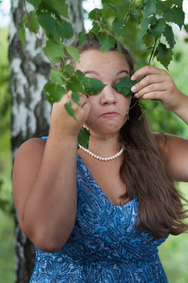 Nastoletnia dziewczyna zakrywa ona oko brzozy liście obrazy royalty free