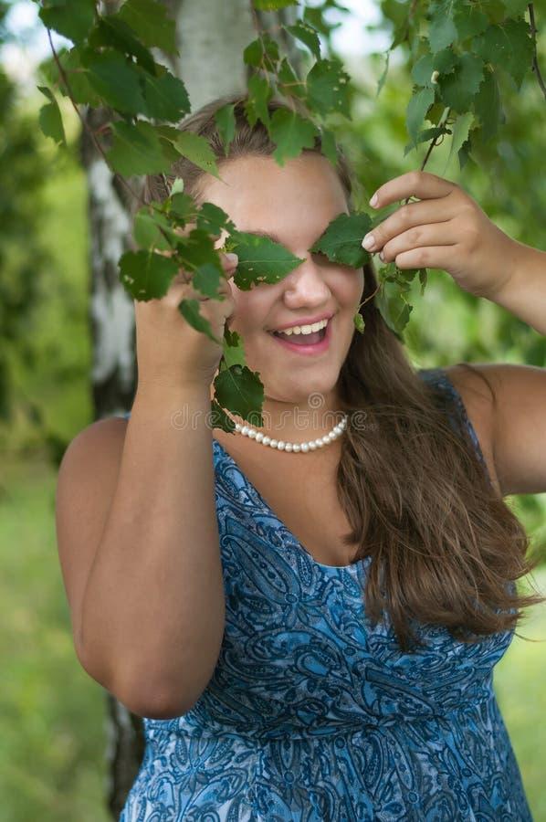 Nastoletnia dziewczyna zakrywa ona oko brzozy liście fotografia stock