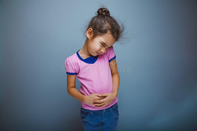 Nastoletnia dziewczyny dziecka żołądka obolałość na szarym tle zdjęcie royalty free