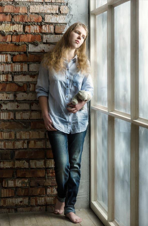 Nastoletnia dziewczyny pozycja przy okno z niedźwiedziem samotny, smutny dziecka Problemy edukacja nastolatkowie zdjęcie royalty free