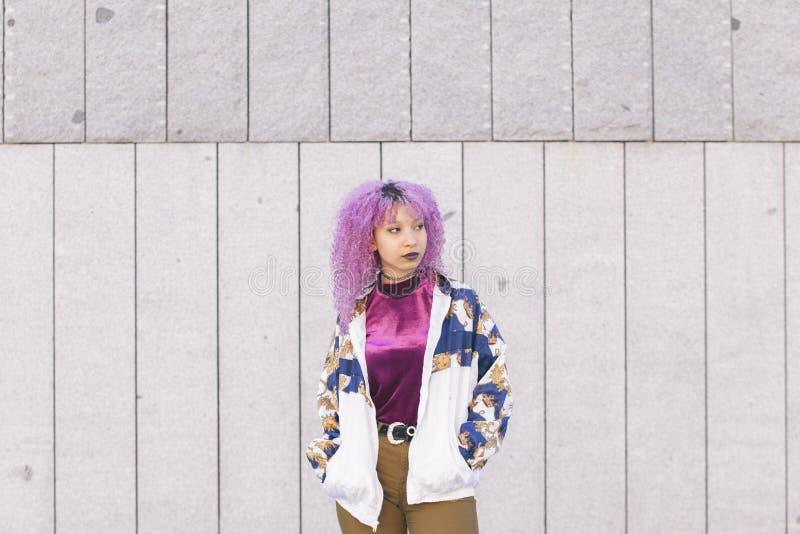 Nastoletnia mieszana biegowa kobieta jest ubranym purpurowego wierzchołek różowego afro włosy i zdjęcie royalty free