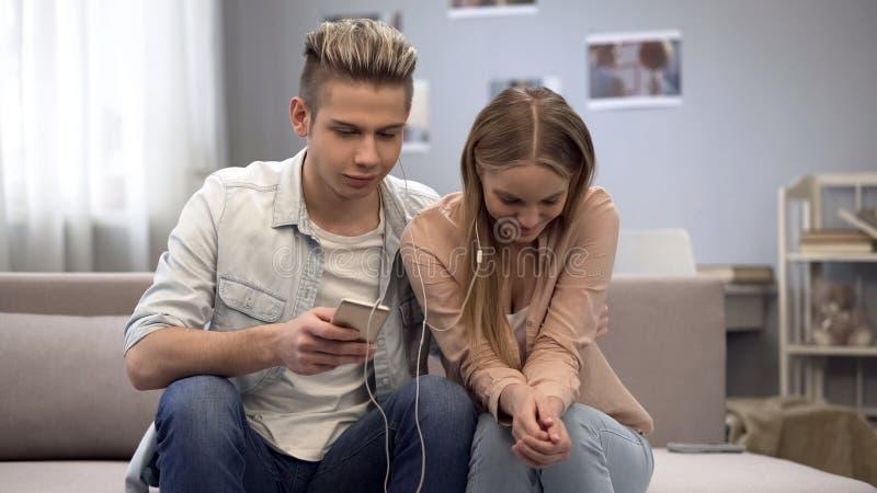 Nastoletnia para słucha muzyka wpólnie komunikować na pierwszy dacie, nieśmiały fotografia stock