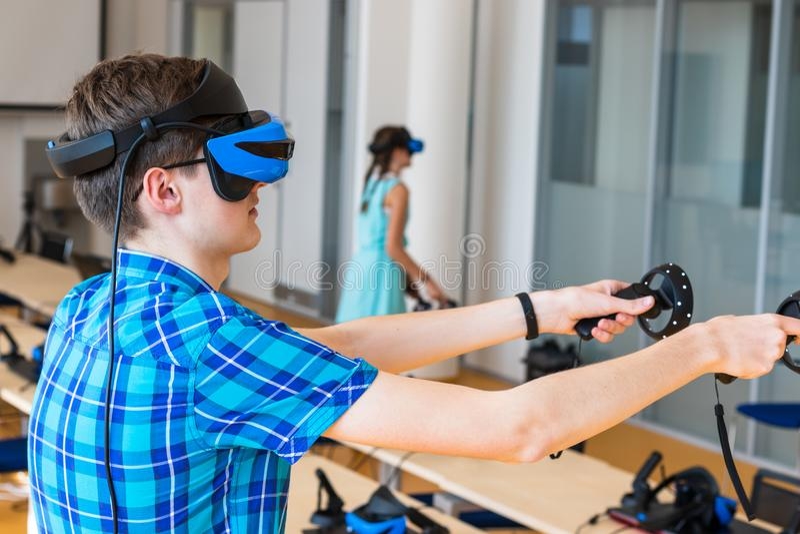 Nastoletnia pełnoletnia chłopiec jest ubranym VR słuchawki, trzyma kontrolerów w rękach i cieszy się nowego doświadczenie w wideo obraz stock
