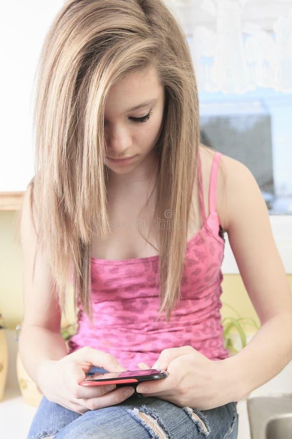 Nastoletnia ręka używać mądrze telefon w domu obraz royalty free