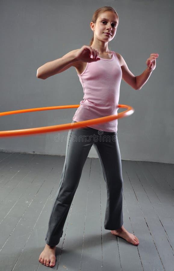 Nastoletnia sportive dziewczyna robi ćwiczeniom z hula obręczem rozwijać mięsień na popielatym tle Mieć zabawę bawić się grę Spor zdjęcia stock