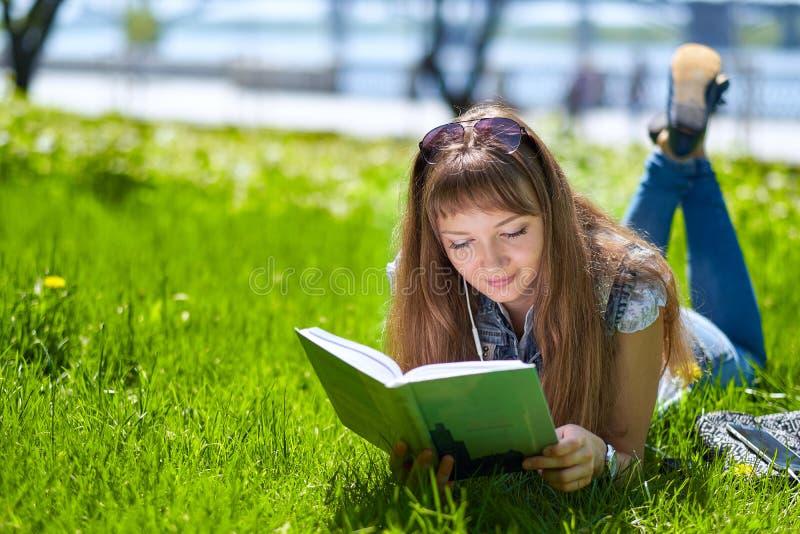 Nastoletnia studencka dziewczyna czyta książkę w parku i lying on the beach na trawie fotografia royalty free