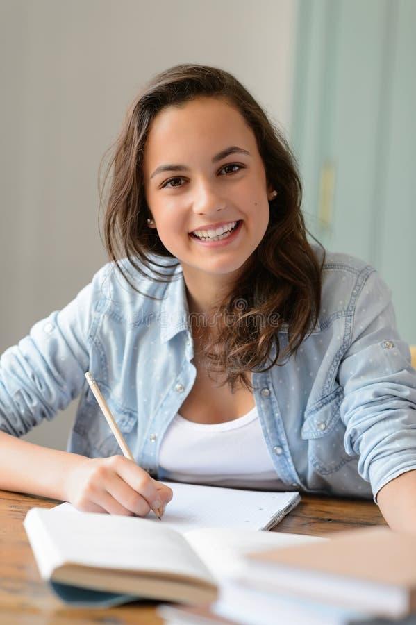 Nastoletnia studencka dziewczyna studiuje w domu uśmiecha się zdjęcie royalty free