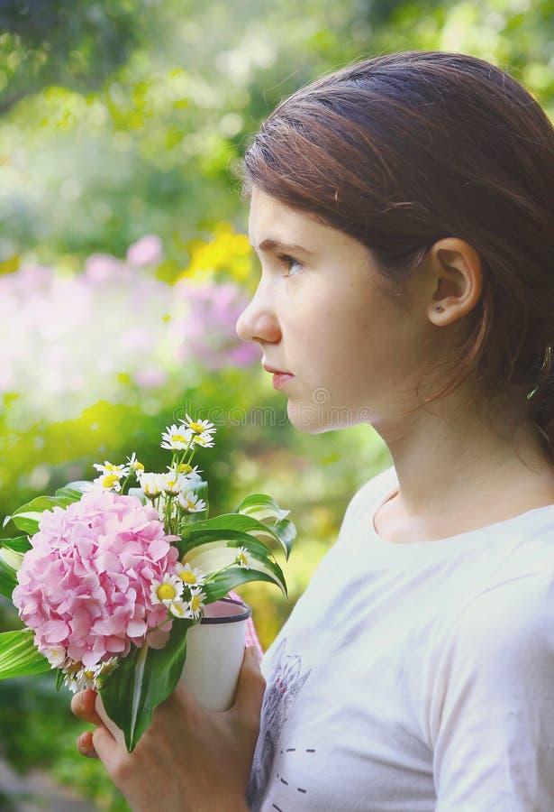 Nastoletnia szczęśliwa dziewczyna z hortensja kwiatami zdjęcia stock