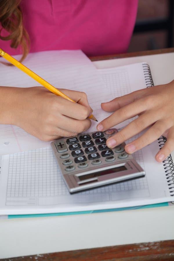 Nastoletnia uczennica Używa kalkulatora Podczas gdy Pisać zdjęcie royalty free