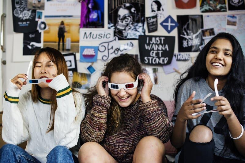 Nastoletnie dziewczyny jest ubranym 3d filmu eyeglasses cieszy się śmiać się TV i oglądać zdjęcie stock