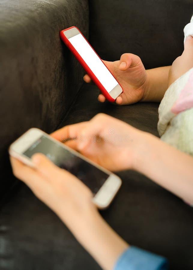 Nastoletnie dziewczyny kłaść na kanapie podczas gdy trzymający mądrze telefon z pustym ekranem w rękach i komunikujący dwie siost fotografia stock