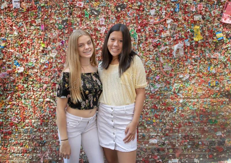 Nastoletnie dziewczyny przed Targową teatru dziąsła ścianą, szczupaka miejsca rynek, Seattle, Waszyngton zdjęcia stock