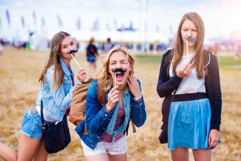 Nastoletnie dziewczyny przy lato festiwalem z sfałszowanym wąsy zdjęcia royalty free