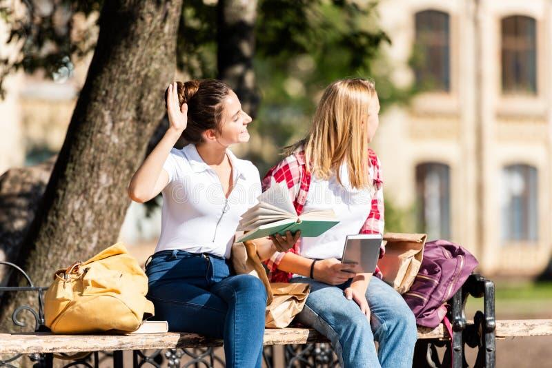 nastoletnie uczennicy siedzi na ławce i czytaniu zdjęcie stock
