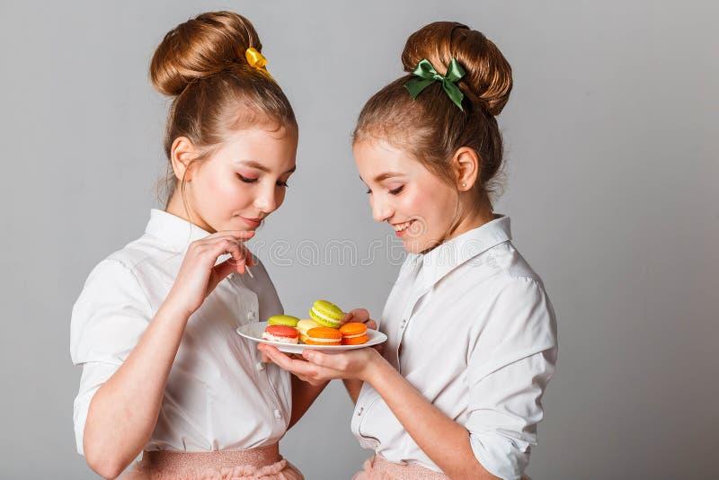 Nastoletnie wzorcowe bliźniak siostry z macaroons obraz stock