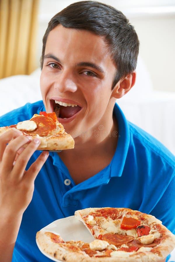 Nastoletniego Chłopaka łasowania plasterek pizza zdjęcia royalty free