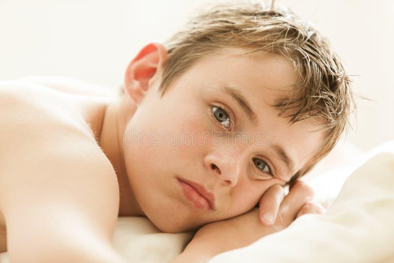 Nastoletniego Chłopaka lying on the beach na łóżku z głową na rękach fotografia stock