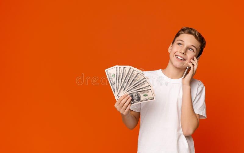 Nastoletniego chłopaka mienia pieniądze banknoty i opowiadać na telefonie komórkowym zdjęcia royalty free