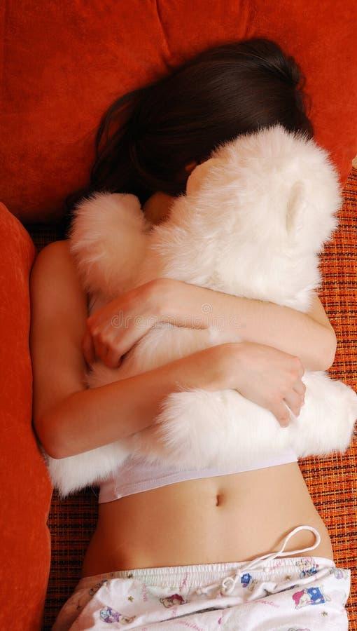 Nastoletniej dziewczyny dosypianie z milutką zabawką w kanapy łóżku obraz royalty free