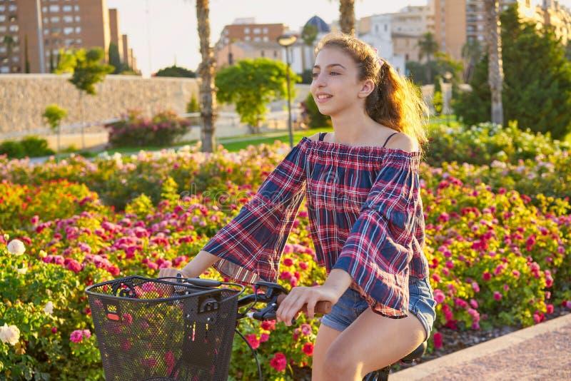 Nastoletniej dziewczyny jeździecki bicykl w mieście kwitnie parka obrazy stock