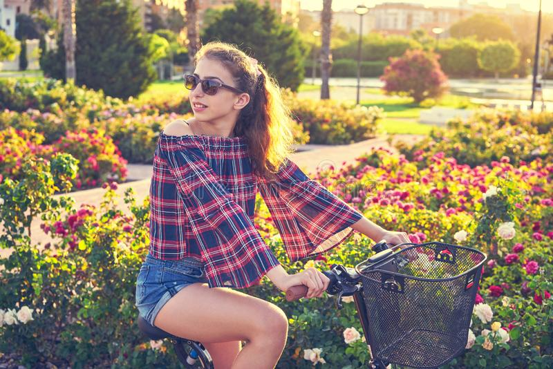 Nastoletniej dziewczyny jeździecki bicykl w mieście kwitnie parka obraz stock