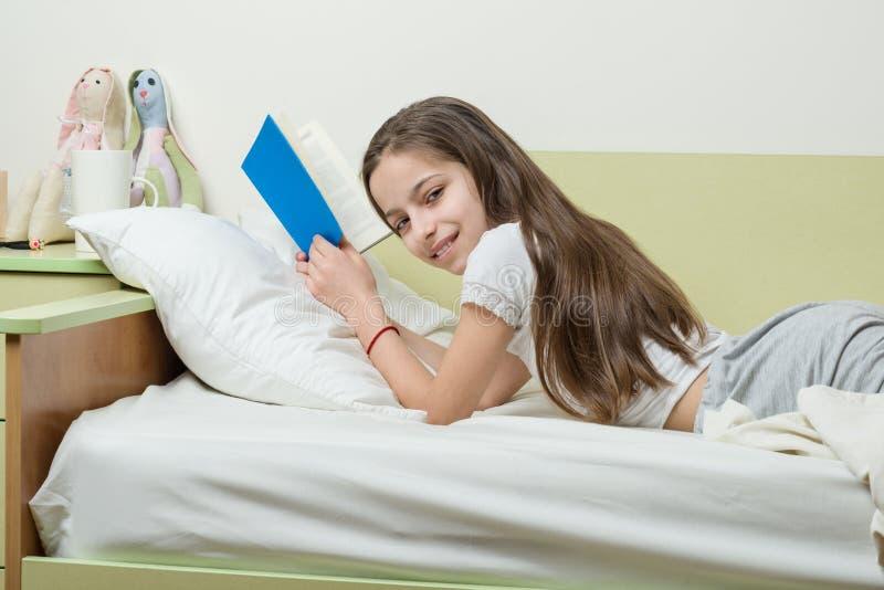 Nastoletniej dziewczyny 10 lat w domów ubraniach czyta książkę na łóżku w jej pokoju obraz stock