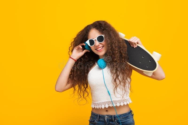 Nastoletniej dziewczyny mienia cruiserboard ono uśmiecha się zdjęcia royalty free